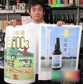 Chủ cửa hàng cầm trên tay tấm áp phích quảng bá cho nhãn hiệu bia giải khát vị sữa bò -Bilk